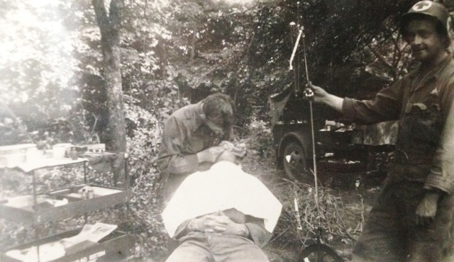 Written on the back of the photo: Somewhere in France, doing dental work on a soldier in an apple orchard. My dental assistant on the right.